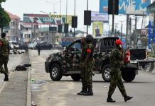 Nigerian soldiers condone a street to restore normalcy