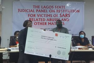 Adebayo Abayomi receiving the N10m compensation on behalf of his family