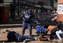 A police officer detains demonstrators in Katlehong, South Africa, today as protests continue following the imprisonment of former South African president Jacob Zuma