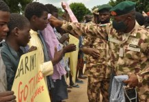 Military officers hand clothes to repentant Boko haram terrorists handed