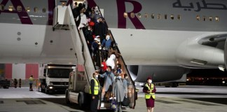 Passengers disembark a Qatar Airways plane arriving from Kabul, Afghanistan, the first international commercial flight since the U.S. withdrawal from Afghanistan, in Doha, Qatar