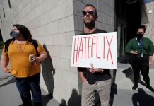 """A man holds a placard as he attends a rally in support of the Netflix transgender employee walkout """"Stand Up in Solidarity"""" to protest the streaming of comedian Dave Chappelle's new comedy special, in Los Angeles, California, U.S"""