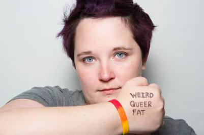 kirsten stands with her arm up - on her hand in sharpie are written the words 'weird, queer, fat' - this photo was titled 'i am not my identity'