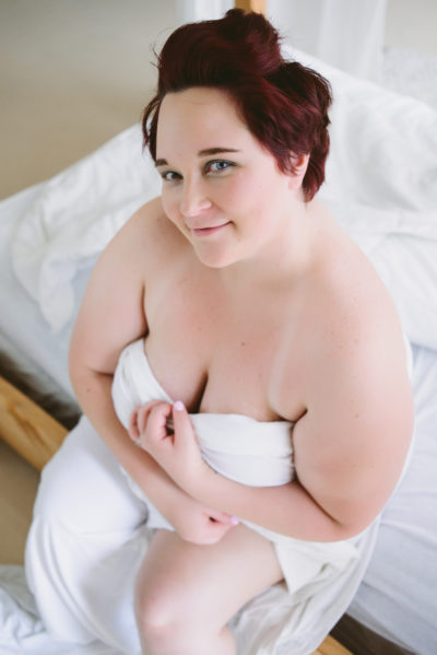 color pic of kirsten sitting on the edge of the white bed wrapped in a white sheet a la a mermaid; short red hair; pic is taken from above so K is looking upwards and smiling; the left hand pulls down some of the sheet for cleavage and the right is nearly hugging her again; left leg pokes out of sheet