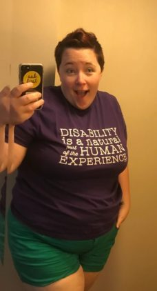 """photo of an overweight genderfluid person wearing green shorts and a purple shirt that says """"Disability is a natural part of the human experience""""; she has short reddish hair; this is a selfie in a mirror with phone visible"""