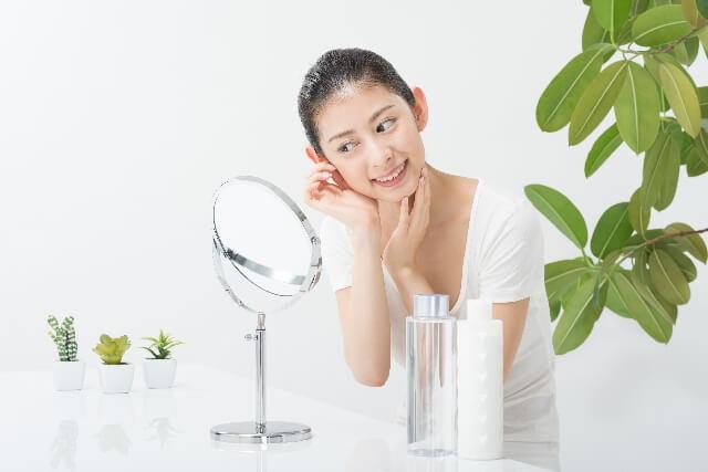 鏡でお肌の調子をチェックする女性