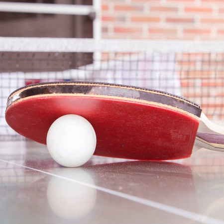 Table tennis bat and ball on table