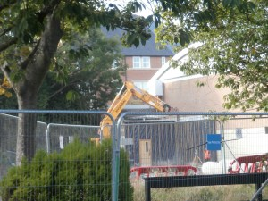 Excavator at work in front of Church High Sports Hall entrance.