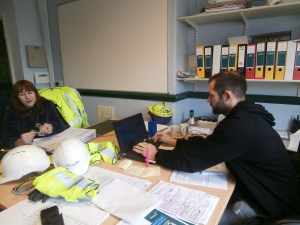 Nick talks to Zoe about metal work at the Project Manager's desk in Westward House.