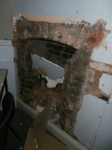 The hearth and chimney piece newly exposed in Room 5.