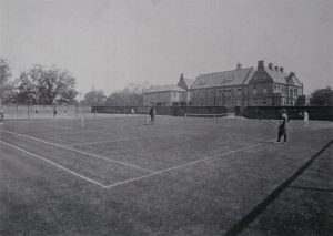 A Church High prospectus image showing the School photographed from the tennis courts in the Hospital grounds. A gate is now clearly visible in the wall and the presence of the Science Laboratory on stilts over the school yard indicates the late 1920s.
