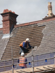 Roof tiles being removed one by one.