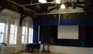 The Church High stage in recent times: black stage-flats, a full lighting rig, overhead projector and screen for assemblies and the lectern was moved to the floor to support laptops.