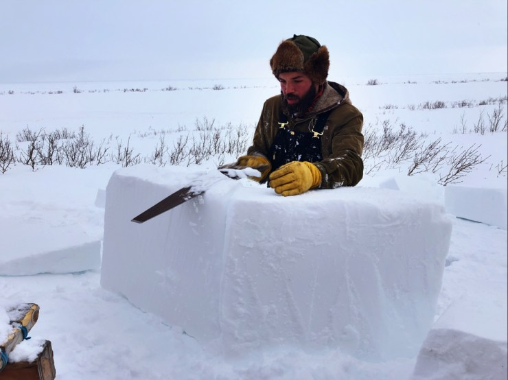 Guide Josh Robson carves snow for a snow blind to hide photographers from the bears.
