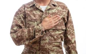 Young soldier with hand on heart standing on white background