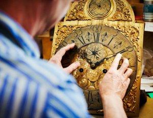 A clock maker working on antique clock