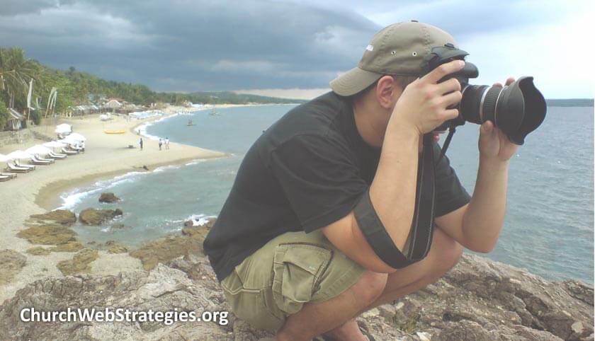 man on coastal cliff taking a photograph