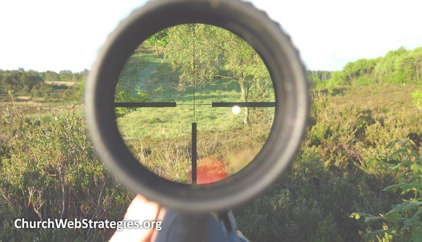 gun scope showing grassy landscape