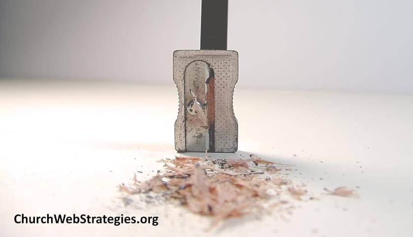 pencil in sharpener with shavings on a table