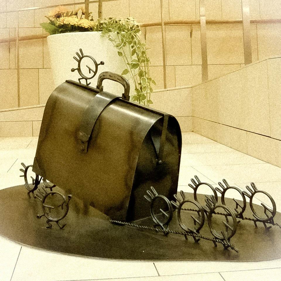 横浜ノースポートモールにオープン時設置されていたアートオブジェ「急ぐヤツら」。忘れ物のバッグや鞄を届けるために駅へと急いでいる彫刻作品です。全て鉄で制作されました。ドクターバッグを運ぶ作品。