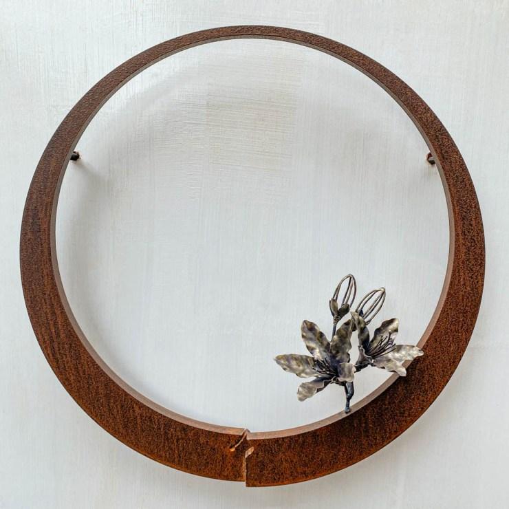 箱根の春を彩るミツバツツジの花を円弧に添えた鉄の彫刻、アート作品です。壁面へ取り付ける仕様になっています。蕾は鍛造した鉄線で表現し軽い印象になっています。円弧は厚みのある鉄を切り出し、下部でズラして表情をつけています。