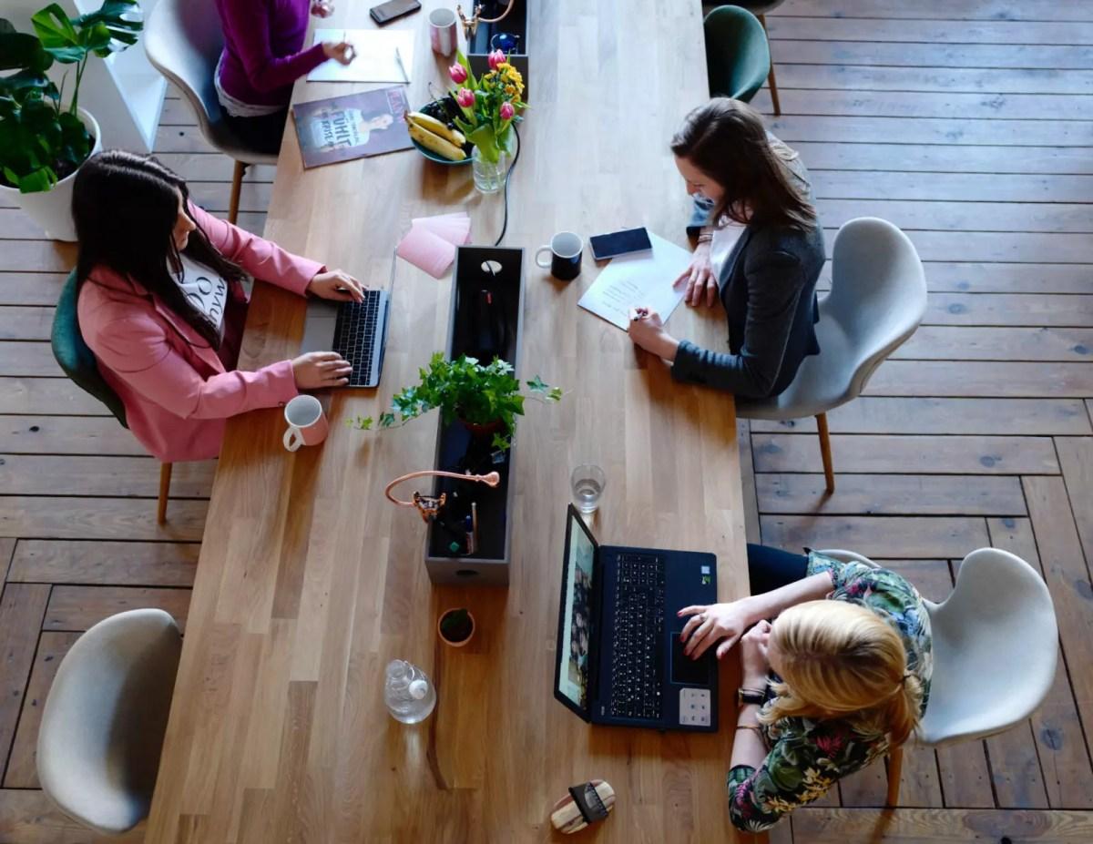 karşılıklı masada çalışan üç kadın