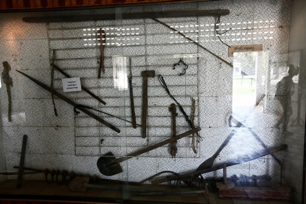 The image of a visitor is reflected in a display case holding iron leg shackles and torture tools used during interrogation sessions at Tuol Sleng prison in Phnom Penh, Cambodia. An estimated 14,000 to 20,000 victims passed through Tuol Sleng from 1975-1979 under the Khmer Rouge. Nearly all of them were eventually murdered in the Killing Fields after two to three months of brutal interrogation, during which they were forced to confess to a list of often imaginary crimes against the regime. More than 500 foreigners were among those imprisoned at Tuol Sleng, including 10 westerners. None of the foreigners survived. March 1, 2012.