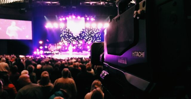 Large camera on tripod, pointed at purple stage and audience; coronavirus