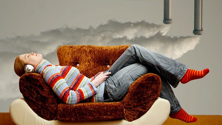 Una ragazza si rilassa sul divano, sullo sfondo dei tubi di scarico.