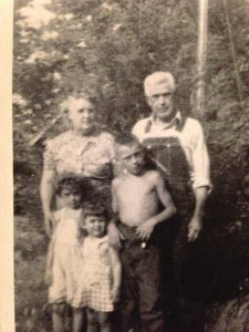 Woman with gray hair wearing floral dress stands next to her husband in coveralls with three grandchildren in front.