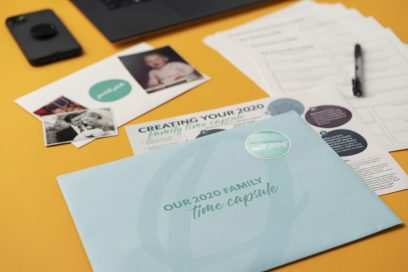 2020 Family Time Capsule Kit by Circa Legacy with mobile phone, photographs, coffee mug, and writing pen.