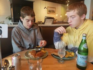 Two teenaged boys eating Cubano sandwiches in Minneapolis restaurant
