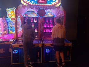 Two teenaged boys placing arcade games