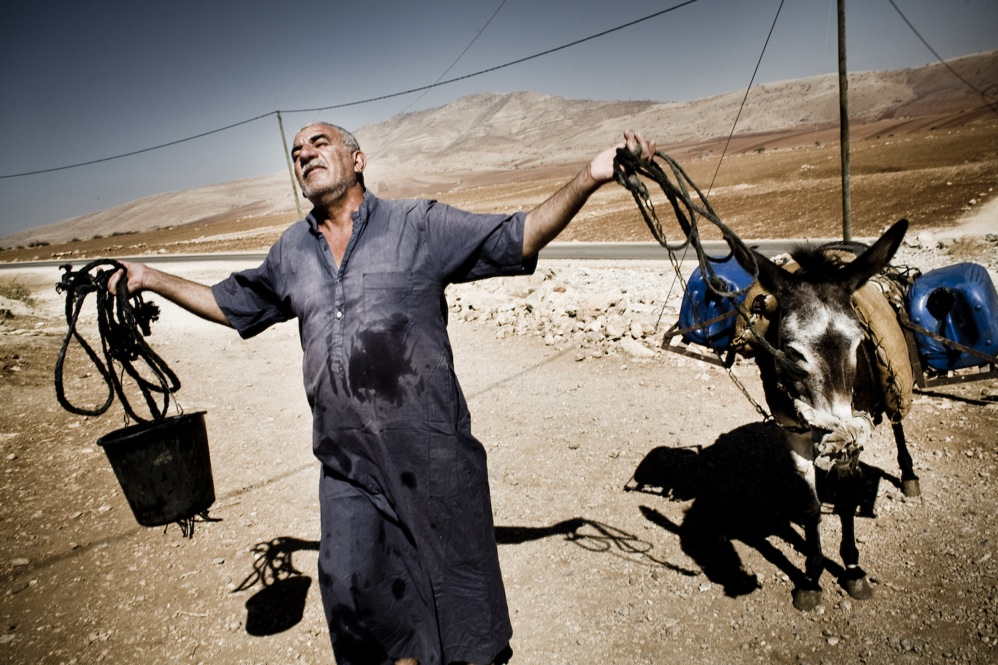 With no nearby sources for water, a farmer waits for a water tanker.