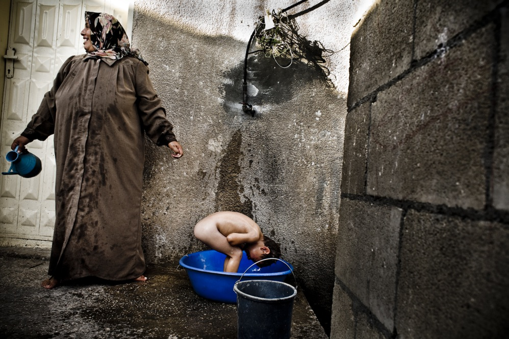 In a village with no central water supply, a boy bathes.