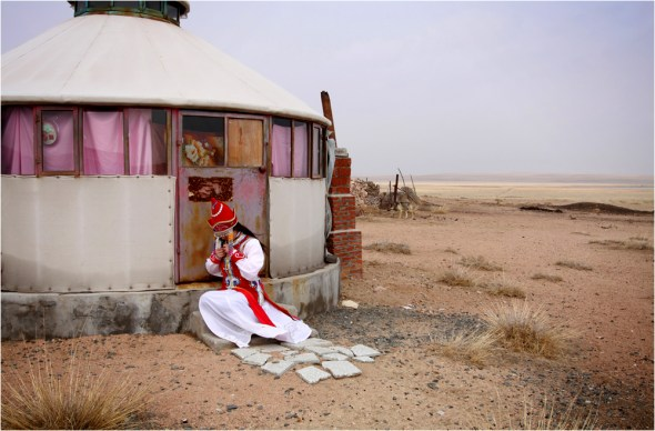 A tourist tries on traditional Inner Mongolian dress on the degraded grasslands.