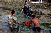 China fishing fish fisherman fishermen draining canal irrigation agriculture food production Liaohe River near Xinmin Liaoning Province
