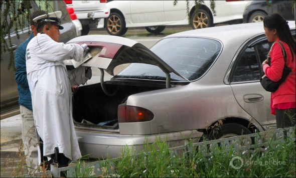 A policeman removes the license plate of an offender of Ulan Bator's strict traffic reduction statute. Minutes later the vehicle was impounded.