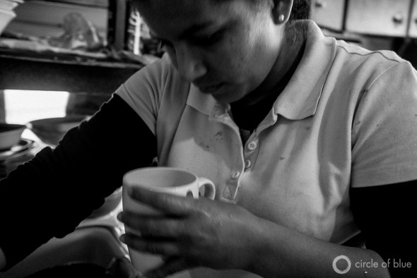 Evilia Robles, inspects her drinking water at her home in Alpaugh. The small farmworker community in California's Central Valley suffers from high levels of arsenic and other contaminates in its water.