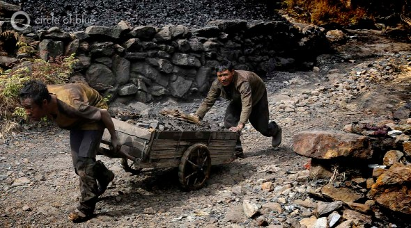 Two miners drag a cart of coal out of a rathole mine south of Shillong. The coal face is at the end of a tunnel over one kilometer long. It takes miners an hour to trudge to the coal face, an hour to mine and fill the cart, and an hour to pull the cart with $2 worth of coal back to the mine entrance.