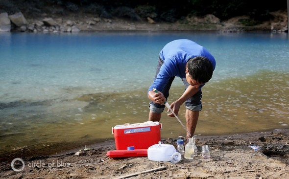 A zoologist with the Meghalaya Pollution Control Board tests the acidity of the Lukha River. The otherwordly blue waters had a pH of 4.5, sufficient acidity to kill fish. (Dhruv Malhota/Contact Press Images for Circle of Blue)