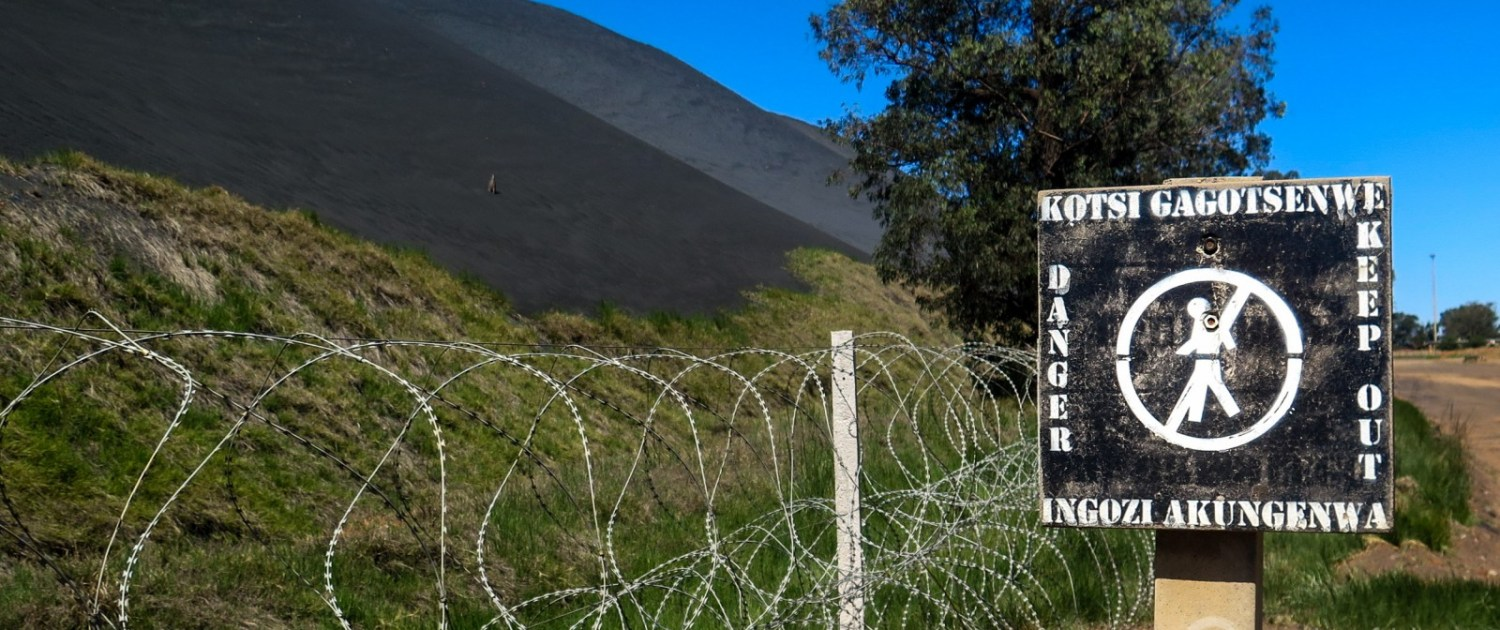 Outside Emalahleni, the center of South Africa coal mining and coal-fired electricity generation, a sign warns of the hazards from interacting with a coal waste pile. Photo © Keith Schneider / Circle of Blue