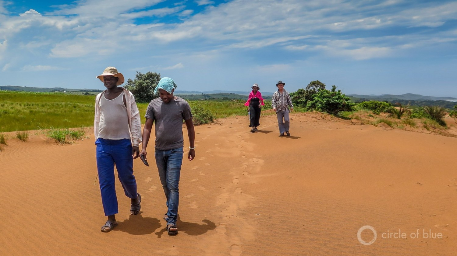 Three leaders of the Amadiba Crisis Committee, which has opposed beach mining and a new national highway since the group's founding in 2007, tour the area of the proposed mine in January. From left to right they are Zwelidumile Yalo, Mzamo Dlamini and Nonhle Mbuthuma. Dick Forslund, far right, is Mbuthuma's husband. Photo © Keith Schneider / Circle of Blue