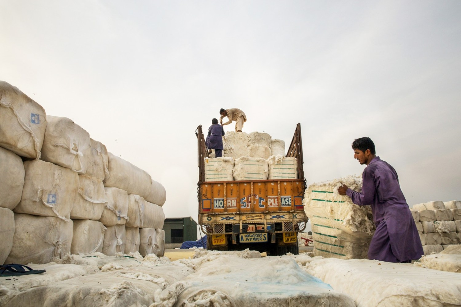 Workers unload cotton bales at the Wagah-Attari Cargo Terminal on the border of India and Pakistan. Dry conditions in Pakistan during the past year wilted crops and forced the textile industry to import $US 4 billion of cotton. Photo courtesy Asian Development Bank via Flickr Creative Commons