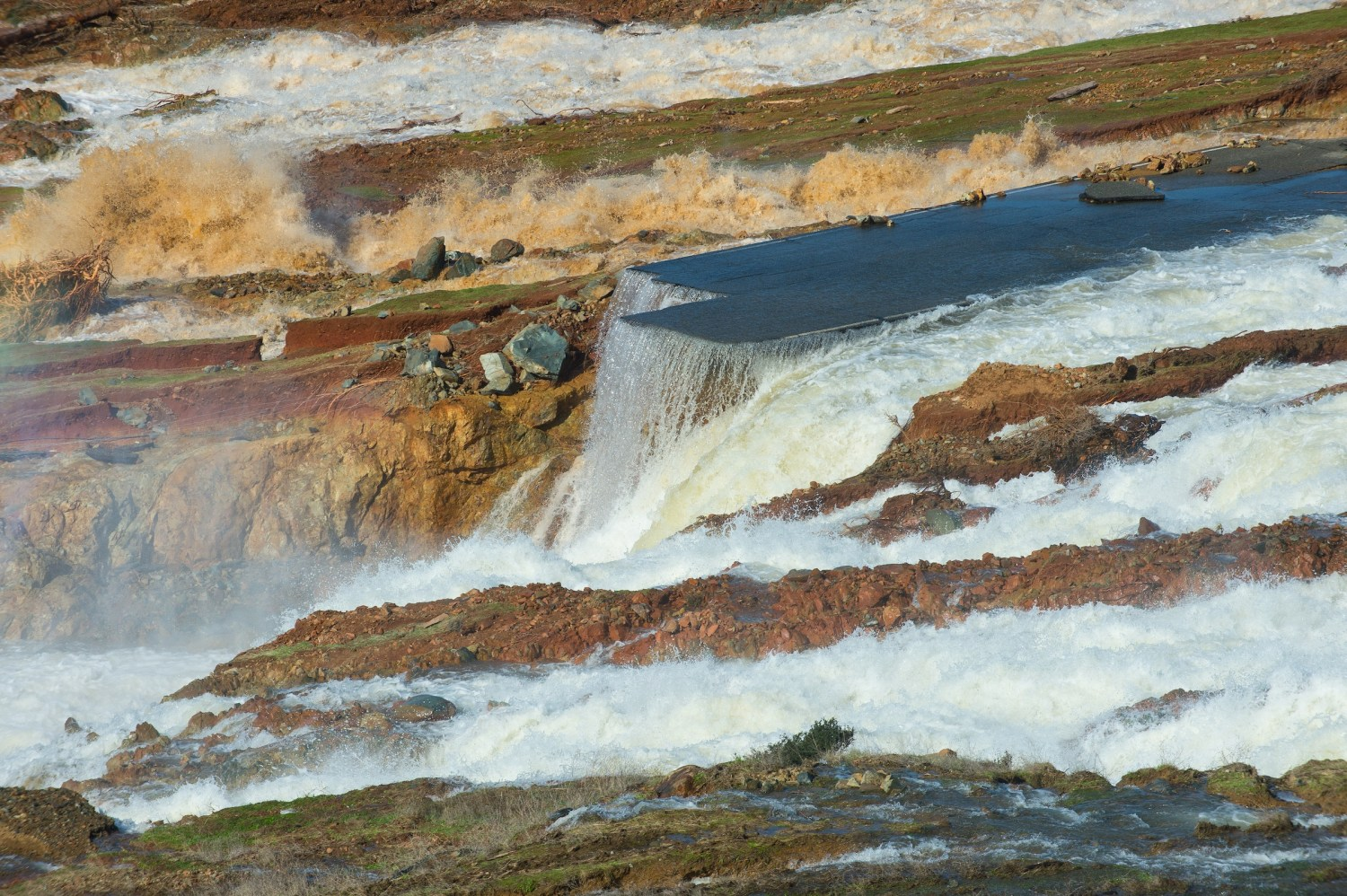 Water from the Oroville Dam auxiliary spillway has eroded the roadway just below the spillway. Photo courtesty of Kelly M. Grow/ California Department of Water Resources