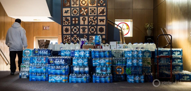 Bottled water awaits pickup in Flint, Michigan. Photo by J. Carl Ganter.