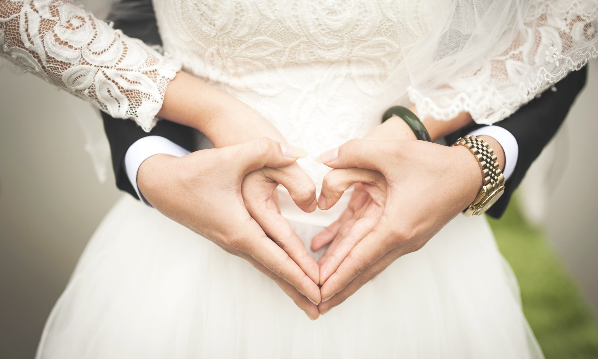 Husband and wife create heart shape with hands to celebrate marriage. Marriage Ceremony