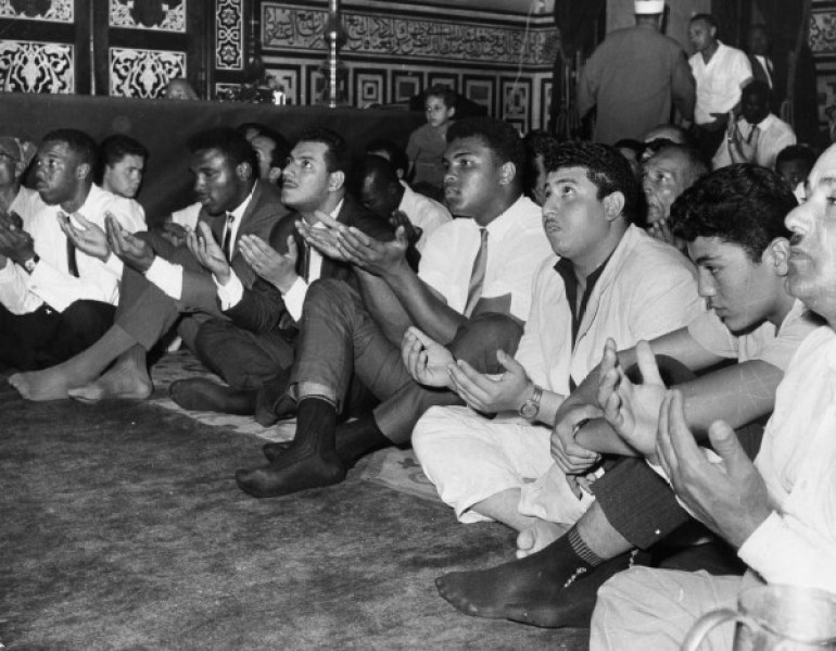 June 1964: American boxer Muhammad Ali (4th from R, formerly known as Cassius Clay) prays with his hands open in a crowd at the Hussein Mosque in Cairo, Egypt. He is wearing pants, no shoes, a short-sleeved shirt and a tie. (Photo by Express/Express/Getty Images)