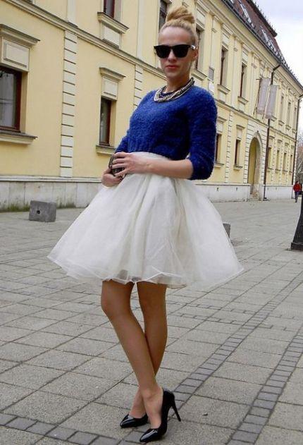 Blusa azul, saia de tule branca e sapato preto. O penteado com coque alto e óculos escuros deram mais charme a produção