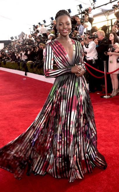 A atriz Lupita nyong'o usou vestido longo de mangas e decote em v, com fundo de flores e listras, no red carpet do SAG Awards